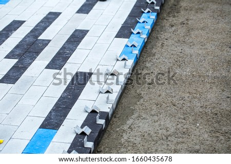 Construction work on pavement. Installation of concrete paver blocks on the sidewalk. The rows of pavement paving are already ready. Should take some time to grip concrete mortar. #1660435678