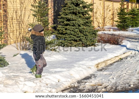 A cheerful, happy boy is playing in the wet spring snow. A European child throws a ball of snow at a friend.