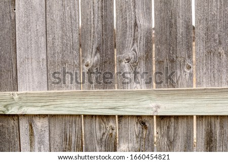 Old, weathered wooden slats make up a fence on the front range of Colorado.  Sun bleached wooden fence pickets with knotholes and weathering.  Open space behind gives a neutral background. #1660454821