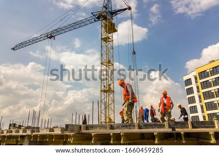 Kyiv, Ukraine - May 3, 2019: Workers working on concrete frame of tall apartment building under construction in a city. #1660459285