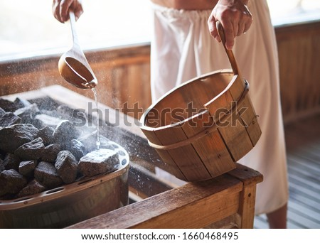 Man pouring water onto hot stone in sauna room. Steam on the stones, spa and wellness concept, relax in hot finnish sauna. #1660468495