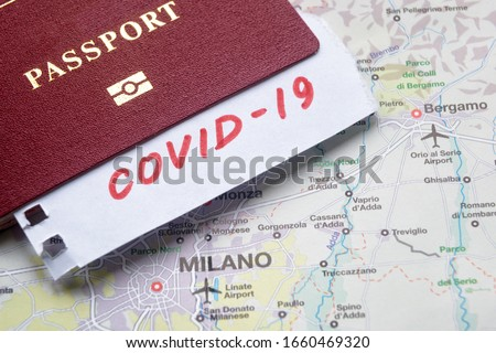 Coronavirus in Italy, pandemic and travel restrictions concept. COVID-19 note and tourist passport on map with Milan. Medical test at border control due to COVID. Novel corona virus outbreak.