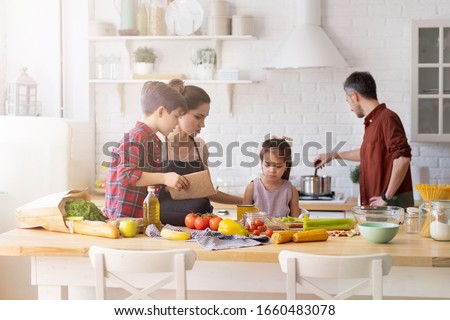 Family with kid spending time on home kitchen in morning. Parent children cooking. Mother and boy son talking to upset daughter. Father mixing boiling dish in pot on stove. Fresh vegetable on table #1660483078