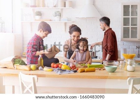 Happy family cooking together on kitchen. Mother and daughter reading recipe to father and son. Dad and boy chopping green vegetable leaf for salad. Home recreation and food preparation on weekend #1660483090