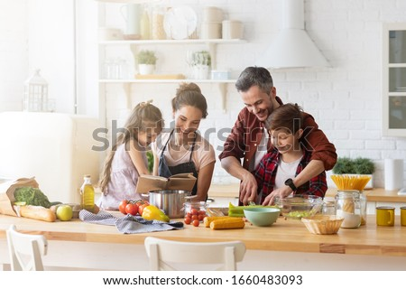 Happy family cooking together on kitchen. Mother and daughter reading recipe to father and son. Dad and boy chopping green vegetable leaf for salad. Home recreation and food preparation on weekend Royalty-Free Stock Photo #1660483093
