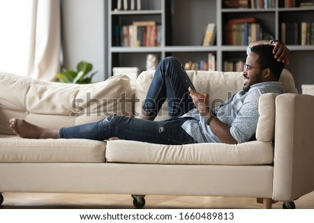 Full length relaxed young african ethnicity man in glasses lying on comfortable couch, enjoying spending weekend leisure time chatting in social network on phone with friends, watching funny videos. #1660489813