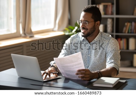 Happy millennial african american businessman in eyewear holding documents, doing paperwork, preparing report or analyzing market research results, working on computer in modern workplace office. Royalty-Free Stock Photo #1660489873