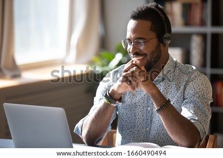 Happy millennial african american man in glasses wearing headphones, enjoying watching educational webinar on laptop. Smiling young mixed race businessman holding video call with clients partners. Royalty-Free Stock Photo #1660490494