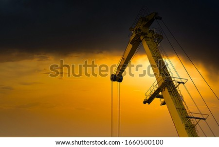 Yellow crane in cargo port translating coal. Industrial scene. Cargo crane at sunset Royalty-Free Stock Photo #1660500100