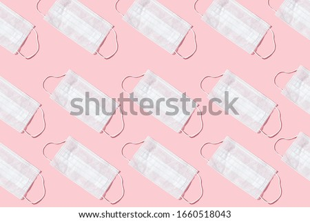 Many medical masks on the pink colored background to cover the mouth and nose for protection from virus and bacteria on a pink background. Epidemic concept. Regular pattern, flat lay. #1660518043