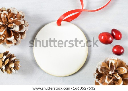 Christmas Ornament Mock Up featuring a round Christmas ornament tied with a red ribbon atop a light gray wood background. Pine cones and fresh cranberries surround the round ornament. Royalty-Free Stock Photo #1660527532