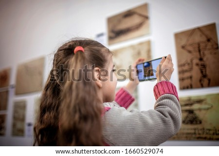 Curious girl exploring a contemporary art exhibition with augmented reality mobile application, future technology in everyday life, indoor lifestyle Royalty-Free Stock Photo #1660529074