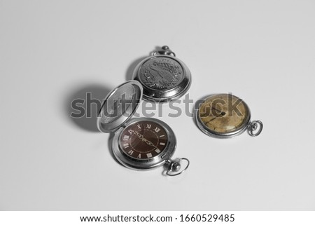 Three old pocket metal watches on a white background. #1660529485