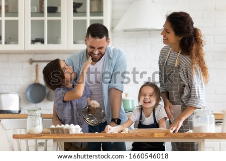 Overjoyed young family with little preschooler kids have fun cooking baking pastry or pie at home together, happy smiling parents enjoy weekend play with small children doing bakery cooking in kitchen Royalty-Free Stock Photo #1660546018