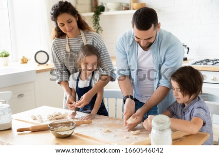 Happy young family with cute little preschooler kids have fun making dough baking pie or pastry in modern kitchen together, overjoyed parents teach small children doing bakery cooking at home Royalty-Free Stock Photo #1660546042