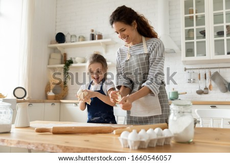 Overjoyed millennial mom have fun baking cookies or pastries with cute little preschooler girl at home, happy young mother teach cook together with small daughter doing bakery in modern kitchen Royalty-Free Stock Photo #1660546057