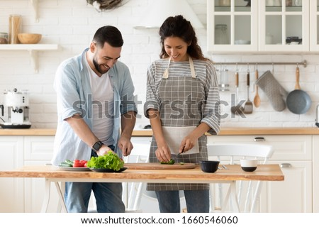 Happy millennial couple stand in modern kitchen cooking salad breakfast or dinner together, smiling young husband and wife vegetarians chop vegetables prepare lunch enjoy morning at home