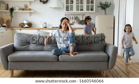 Exhausted young mum sit on couch in kitchen feel unwell tired from ill-behaved loud little children running playing, sick annoyed mother or nanny relax on sofa suffer from headache, parenting concept #1660546066