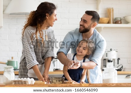 Overjoyed young family with little preschooler daughter have fun doing bakery in kitchen together, happy parents enjoy weekend with small girl child baking biscuits pastries, making pie at home #1660546090