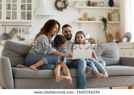 Happy young family with little kids sit on sofa in kitchen have fun using modern laptop together, smiling parents rest on couch enjoy weekend with small children laugh watch video on computer at home #1660546246