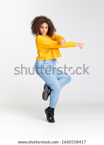 Young African American woman dancing over isolated white background #1660558417