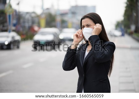 Close up of a businesswoman in a suit wearing Protective face mask and cough, get ready for Coronavirus and pm 2.5 fighting against beside road in background. #1660565059