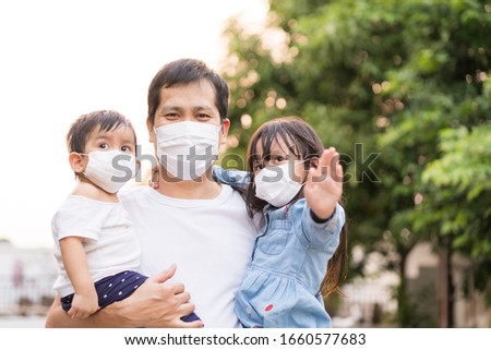 Asian father holding his daughter and son and all of people wear a mask to protect the corona virus and pm 2.5 dust in air, concept of people living in the crisis of covid-19 and air pollution problem #1660577683