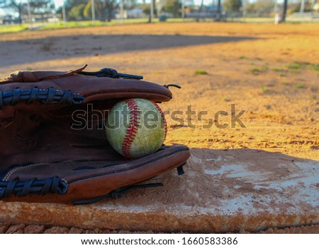 This is a picture of a baseball inside a glove on top of the pitchers mound. The camera is directed towards home plate.