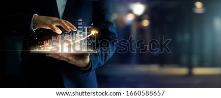 Businessman holding tablet analyzing sales data and economic growth graph chart, Business strategy and planning, Digital marketing and stock market.  Royalty-Free Stock Photo #1660588657