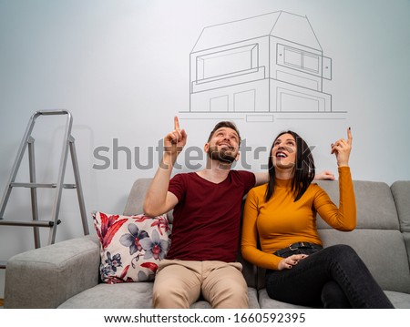 Man and woman sitting on sofa dreaming about new home, dreams come true  #1660592395