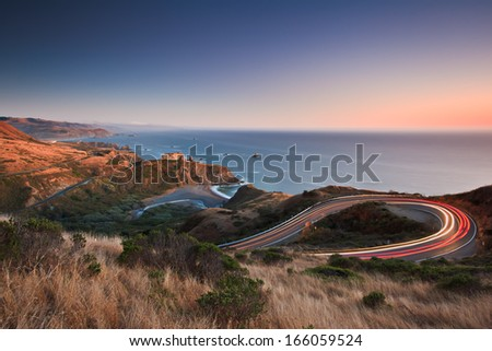 After sunset on the Pacific Ocean looking down the famous highway 1 as evening traffic travels in both directions.  Royalty-Free Stock Photo #166059524