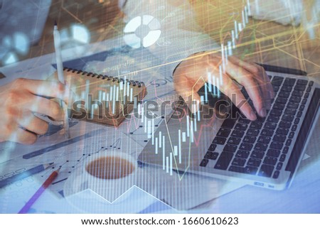 Forex graph with businessman working on computer in office on background. Concept of hardworking. Double exposure. #1660610623