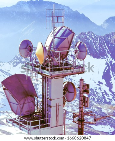 cellular radio tower with antennas in snowy mountains #1660620847