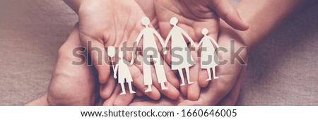 Adult and children hands holding paper family cutout, family home, adoption, foster care, homeless support, family mental health, autism support, domestic violence, social distancing concept #1660646005