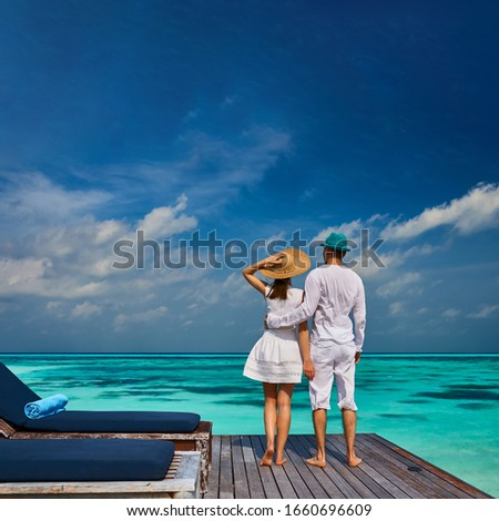 Couple in white on a tropical beach jetty at Maldives #1660696609