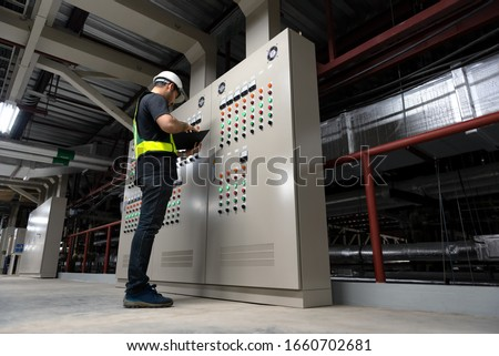 Electrical Engineer team working front HVAC control panels, Technician daily check controls system for security functions in service room at factory. Heating,Ventilation,Air Conditioning. Royalty-Free Stock Photo #1660702681