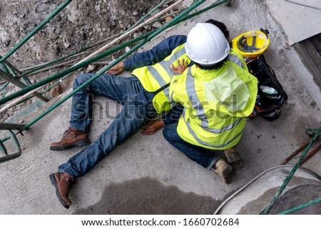 First aid support accident at work of construction worker at site. Builder accident falls scaffolding on floor, Safety team helps employee accident. #1660702684
