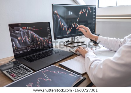Stock exchange market concept, Business investor trading or stock brokers having a planning and analyzing with display screen and pointing on the data presented and deal on a stock exchange. #1660729381
