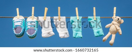 Baby clothes and accessories weigh on the rope after washing in the open air. Selective focus. nature. #1660732165