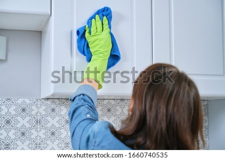 Woman in gloves with rag washing, cleaning, polishing furniture doors on kitchen, cleaning house #1660740535