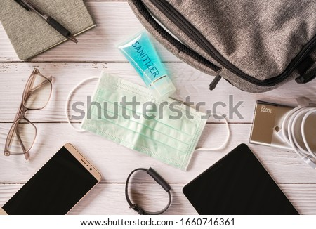 Top view or flat lay of face mask ,sanitizer hand gel to protect against Coronavirus or COVID-19 and neccessary items for daily life and working , Today's personal item  for health protection concept #1660746361