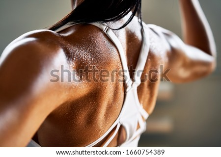 Close up of woman back with flexing her muscles in sweat on skin after workout. Female bodybuilder with perfect biceps                           #1660754389