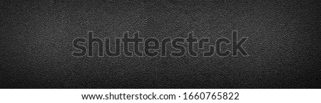 Ultra wide rough black surface. Panoramic background with darkened edges. Texture of flat and grainy sandpaper or panorama of uneven wall material. #1660765822