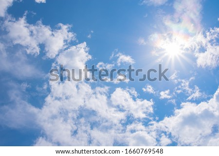 Beautiful Sunny Sky Background with White Clouds. Shining Sun at Clear Blue Sky. Summer Background with Sunlight and Clouds on Blue Sky. Royalty-Free Stock Photo #1660769548