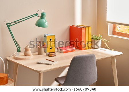 Chair placed near table with lamp and colorful stationery in cozy home office in morning Royalty-Free Stock Photo #1660789348