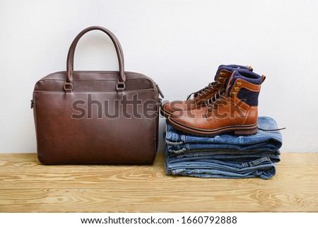 Brown leather boors shoes Stack of different jeans with brown handbag on wooden background    #1660792888