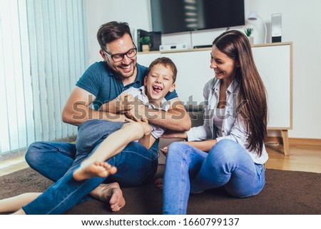 Family time.Mother,father and son having fun at home. #1660799137