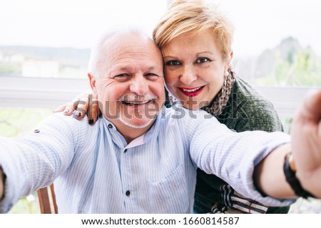 A mature couple takes a selfie with their mobile phone on the terrace of their house
