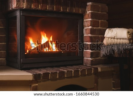 Stack of knitwear near fireplace with burning wood indoors. Winter vacation