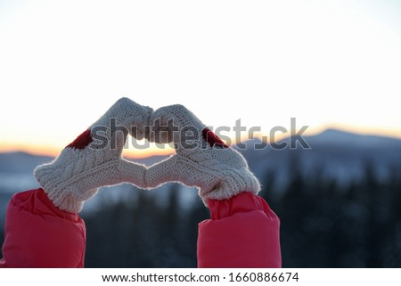 Woman making heart with her hands in mountains at sunset, closeup. Winter vacation #1660886674